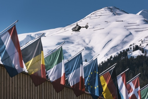 Helicopter flies above flags against mountain backdrop.