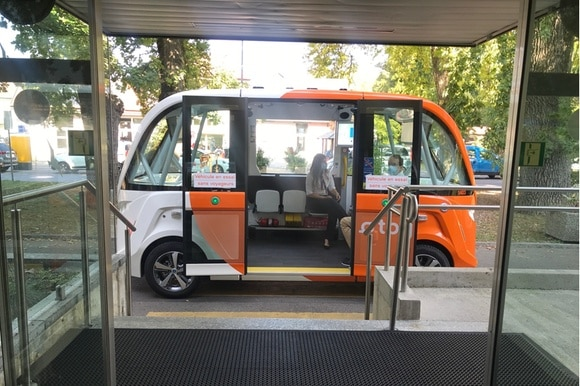 A driverless shuttle in front of the hospital