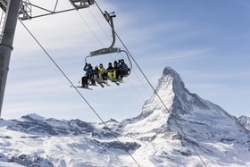 Skiers on ski lift with Matterhorn backdrop