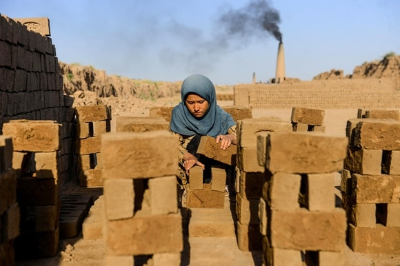 Girl collecting bricks as a labourer at a brick factory in India