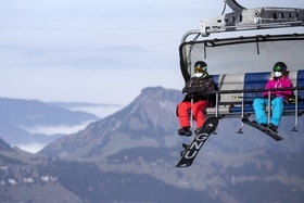 snowboarder and skier on lift