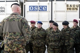 Female member of the Swiss armed forces in front of OSCE container