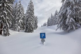 A parking sign almost covered in snow.