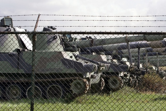 Tanks parked behind barbed wire