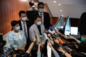 Masked people in front of reporters