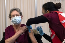 Woman looking pained as she gets a jab