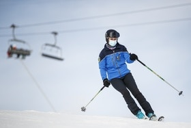 Policewoman on skis, wearing a hygiene mask