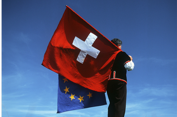 man carrying Swiss and EU flags