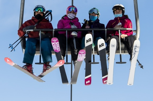 masked people on ski lift