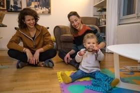 Ambra joue avec une montre assise parterre entourée de ses deux mamans