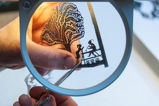 cutting paper under a magnifying glass