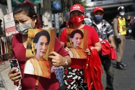 Burmese living in Thailand hold pictures of Myanmar leader Aung San Suu Kyi.