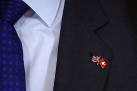 suit, tie and pin with Swiss and UK flags
