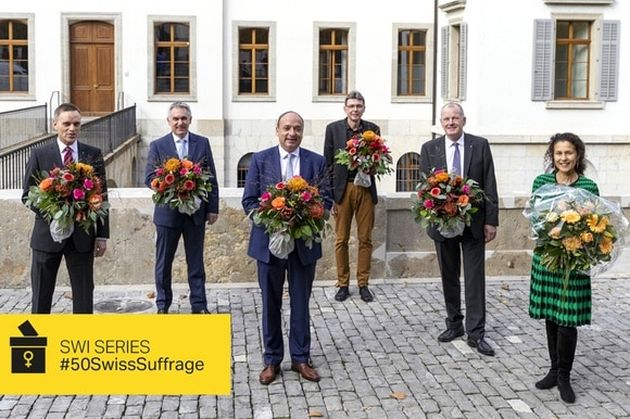 5 men and 1 woman, all holding flowers