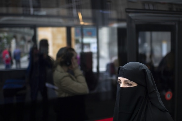 Woman in black burka sitting in public transport