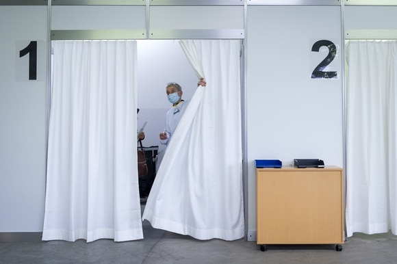 Doctor pulling back a curtain