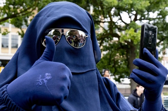 woman wearing blue burka and sunglasses