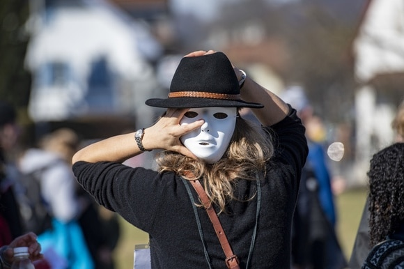 Demonstrator with white mask and hat