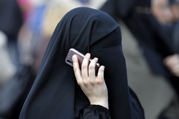 Woman with face covered makes telephone call