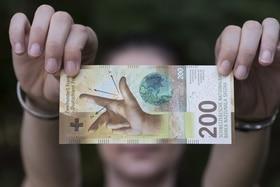 Una mano sostiene un billete de 200 francos suizos