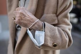 Una máscara protectora cuelga de la muñeca de una persona mayor.