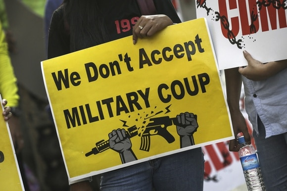 A demonstrator holds a placard during a protest against military coup in Yangon, Myanmar,