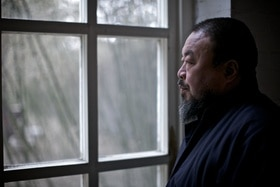 Ai Weiwei looking through a window