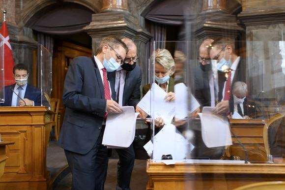 Group of parliamentarians in the Swiss senate comparing documents