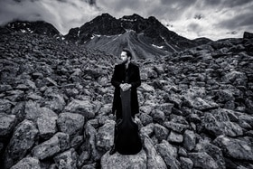 Florian Fox in front of a mountain with his guitar