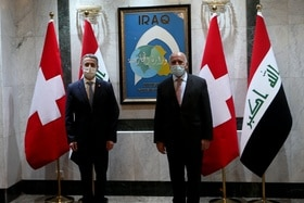 Two masked men in front of flags
