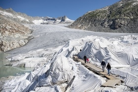 Tarpaulins covering part of a glacier, and people walking across them.