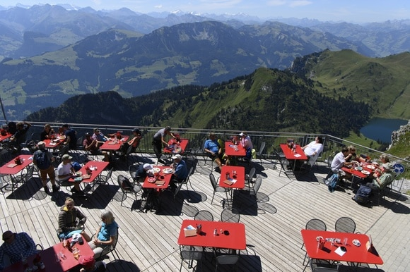 Terrace restaurant with panorama and people sitting at tables.