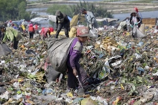 A boy aged 7 collects recyclable materials at a dumpsite in Marelan, Medan, North Sumatra Province, Indonesia.