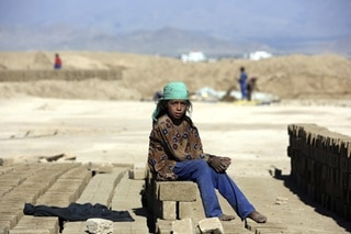 Amina, 9 years old, poses for a photograph as she works at a local brick factory on the outskirts of Kabul, Afghanistan.