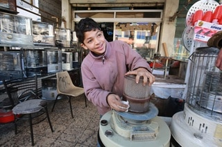 Jordanian teenager, Omar, 14, fixes a kerosene heater in a workshop where he works in Amman.