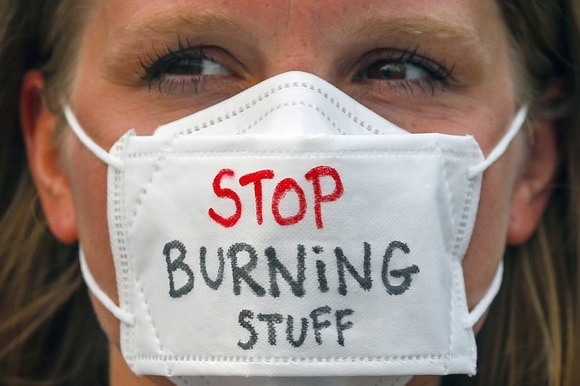 climate change protester with mask that reads stop burning stuff
