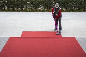 Man sweeps red carpet
