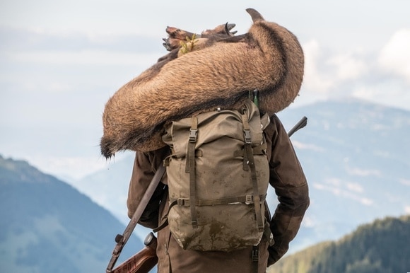 A hunter with a deer on his shoulders