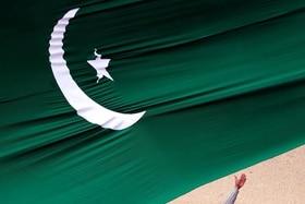 Flag of Pakistan and hand beneath