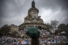 Passant mit Regenschirm vor Gedenkmal